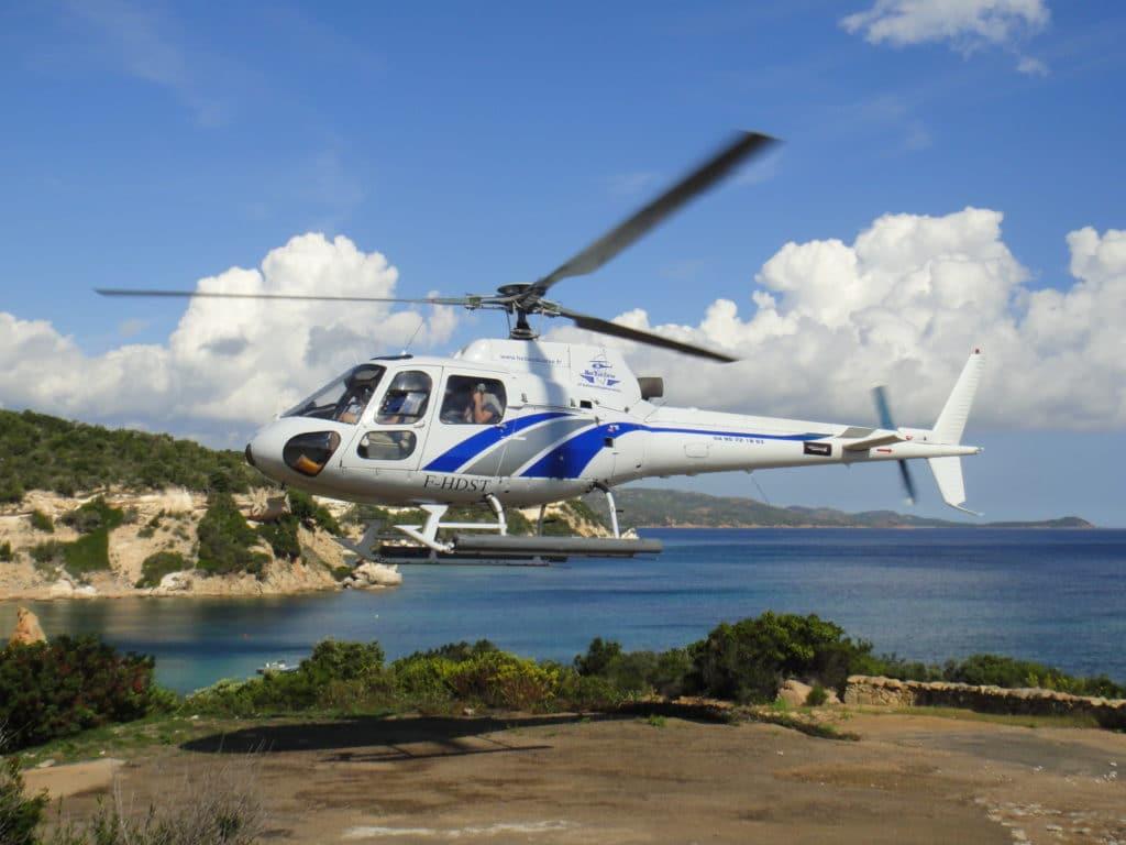 Un hélicoptère décolle avec en arrière plan les superbes paysages de la Corse du sud
