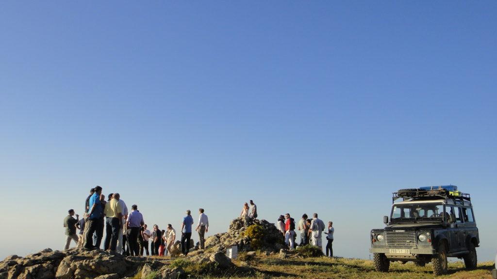 Un 4x4 effectue une pause en haut d'un col laissant les participants admirer le paysage