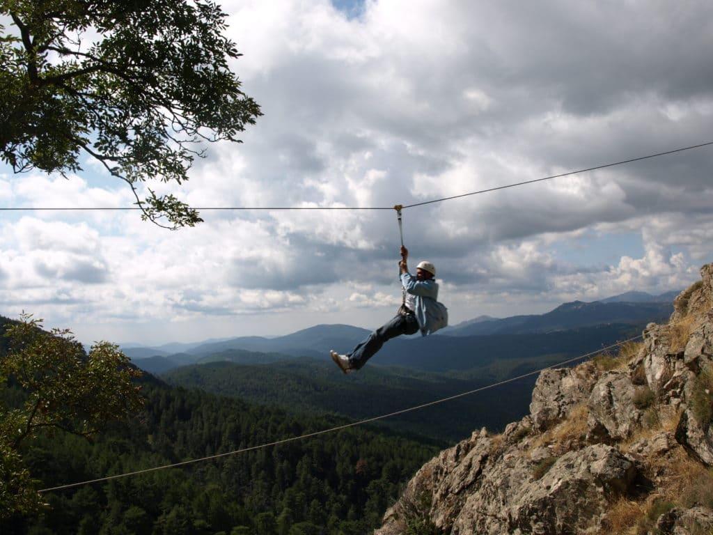 Un participant glisse sur un tyrolienne au dessus du vide