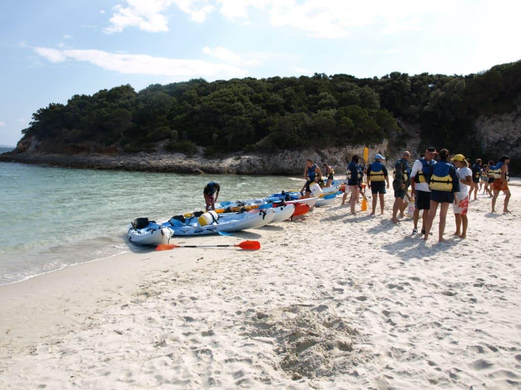 Départ en kayak depuis une plage de sable blanc