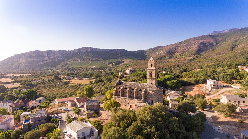 Le village et l'église de Patrimoniu avec en arrière plan les vignes de la région